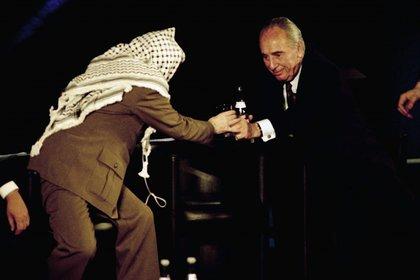 Shimon Peres le sirve agua a al líder palestino Yasser Arafat en un encuentro en la UNESCO sobre Medio Oriente. Paris , 1995 (AP)