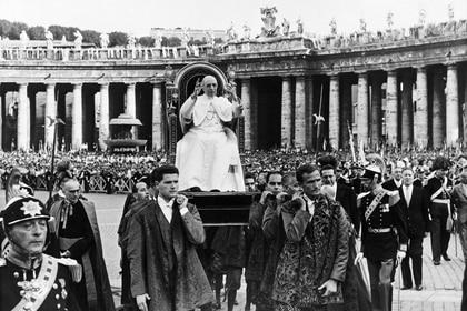 (ARCHIVOS) Esta foto de archivo tomada el 27 de agosto de 1957 muestra al Papa Pío XII, jefe de la Iglesia Católica desde el 2 de marzo de 1939 hasta su muerte el 9 de octubre de 1958, bendiciendo a los fieles durante el congreso de Jóvenes Trabajadores Cristianos en la Plaza de San Pedro en el Vaticano. (Foto por - / AFP)