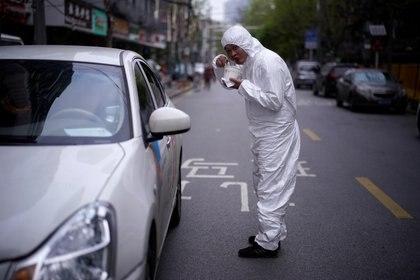 Un hombre con un traje protector come noodles en Wuhan (REUTERS/Aly Song)