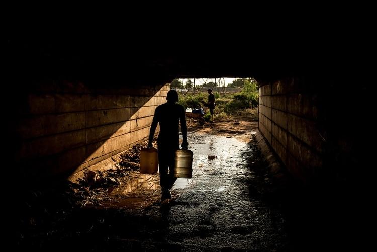 Un grupo de personas recogían agua de una tubería ubicada debajo de un puente en Maracaibo. (Meridith Kohut para The New York Times)