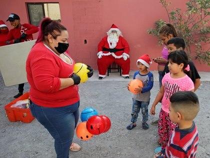 Alberto Molina se sienta vestido de Papá Noel mientras sus familiares distribuyen juguetes a niños en situación de pobreza en Monterrey, México (REUTERS/Daniel Becerril)