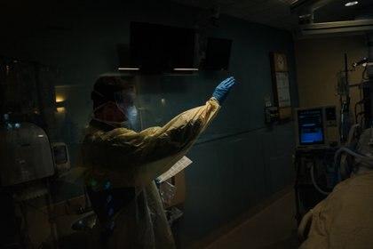 El padre Ryan Connors administra un sacramento católico, la unción de los enfermos, a un paciente con COVID-19 en el Centro Médico St. Elizabeth en Brighton, Massachusetts (Ryan Christopher Jones / The New York Times)