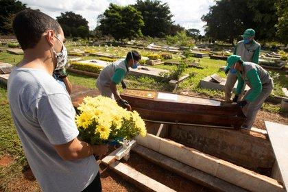Empleados preparan a víctimas de covid-19 para ser enterrados, en el cementerio de Campo da Esperança, en Brasilia ( EFE/Joédson Alves/Archivo)