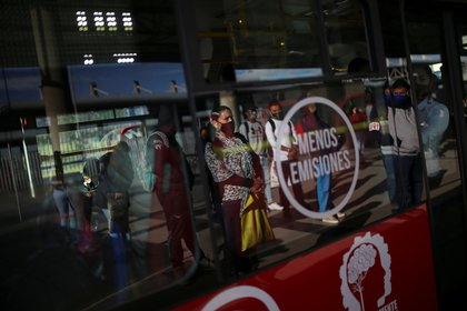 People wearing protective masks due to the ongoing coronavirus disease (COVID-19) outbreak, are seen reflected in a bus window at a station of the TransMilenio public transport system after the mayor's office ended the quarantine in Bogota, Colombia August 27, 2020. REUTERS/Luisa Gonzalez