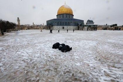 Musulmanes rezan junto a la Cúpula de la Roca durante una mañana nevada en la Ciudad Vieja de Jerusalén, el 18 de febrero de 2021. REUTERS / Ammar Awad