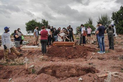 Familiares lloran la muerte por covid-19 de un ser querido, durante su entierro, el 13 de abril de 2021, en un cementerio del norte de Río de Janeiro (EFE/André Coelho)