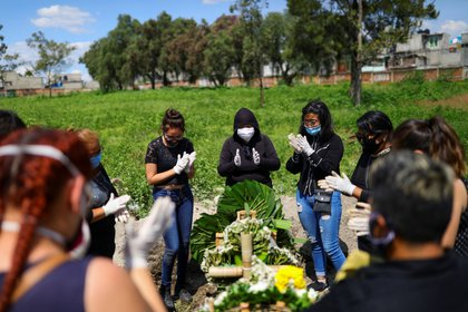 Women and family members say goodbye with applause to Natalia, 85, who died of the coronavirus disease (COVID-19), during her funeral at the San Lorenzo Tezonco cemetery, as the coronavirus disease (COVID-19) outbreak continues, in Mexico City, Mexico August 5, 2020. REUTERS/Edgard Garrido