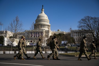 Members of the National Guard walk past a security perimeter outside the U.S. Capitol as preparations are made ahead of the presidential inauguration in Washington, D.C., U.S., on Saturday, Jan. 16, 2021. The U.S. capital is getting even more fortified with the help of patrolling by uniformed National Guard forces as federal, state and local officials brace for a worst-case scenario of violence tied to the Jan. 20 inauguration.