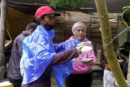 Migrantes venezolanos con máscaras faciales debido al brote de la enfermedad coronavirus (COVID-19) reciben alimentos donados en un punto de atención para migrantes en las carreteras colombianas