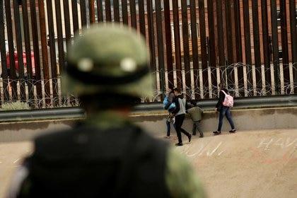 Un soldado de la Gn observa a un grupo de migrantes después de cruzar ilegalmente a El Paso, Texas, para entregarse a agentes de la Patrulla Fronteriza (Foto: Reuters)