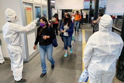 Usuarios del Metrobús pasan un filtro de seguridad y desinfección donde personal de Seguridad Pública les toma la temperatura y les aplica gel antibacterial para poder ingresar a las instalaciones del sistema de transporte de Ciudad de México
