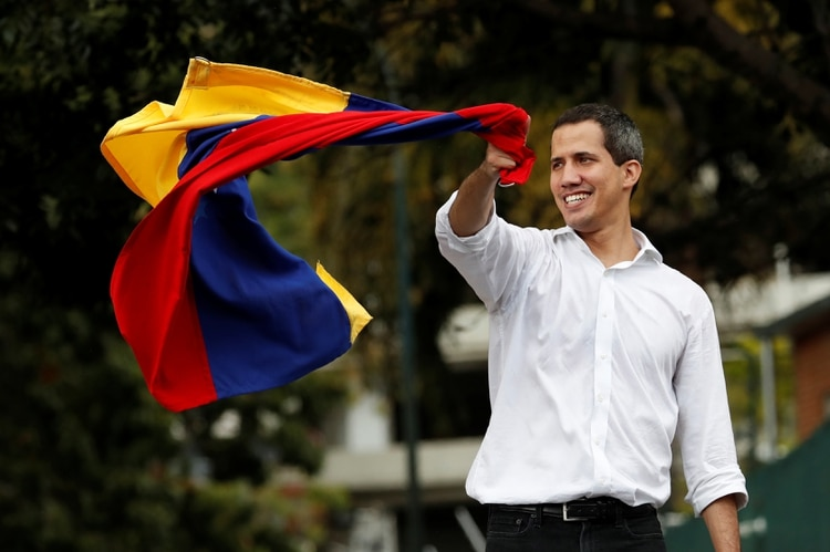 El líder de la oposición venezolana Juan Guaidó, a quien muchos países han reconocido como el legítimo gobernante interino del país, ondea la bandera venezolana en una reunión con partidarios cerca de la embajada de Bolivia en Caracas, Venezuela, el 16 de noviembre de 2019. (REUTERS)