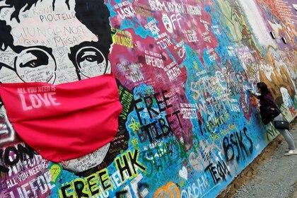 El legendario mural de John Lennon cubierto de graffitis en una calle de Praga, en la República Checa, fue adaptado a esta era de pandemia global.