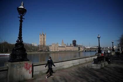 Una mujer camina frente a las Cámaras del Parlamento británico, en la ribera del río Támesis, mientras continúa la propagación del coronavirus en Londres, Reino Unido, el 25 de marzo de 2020. REUTERS/Hannah Mckay