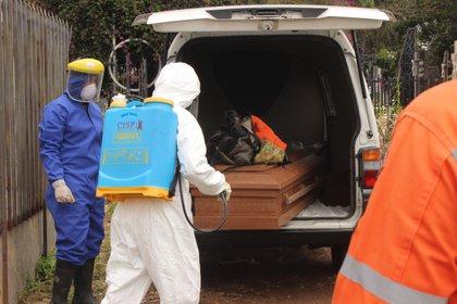 Trabajadores gubernamentales proceden a sacar de un vehículo un féretro con una víctima de COVID-19 para su posterior entierro en el cementerio de San Cristóbal, estado Táchira (Venezuela). EFE/ Johnny Parra/Archivo