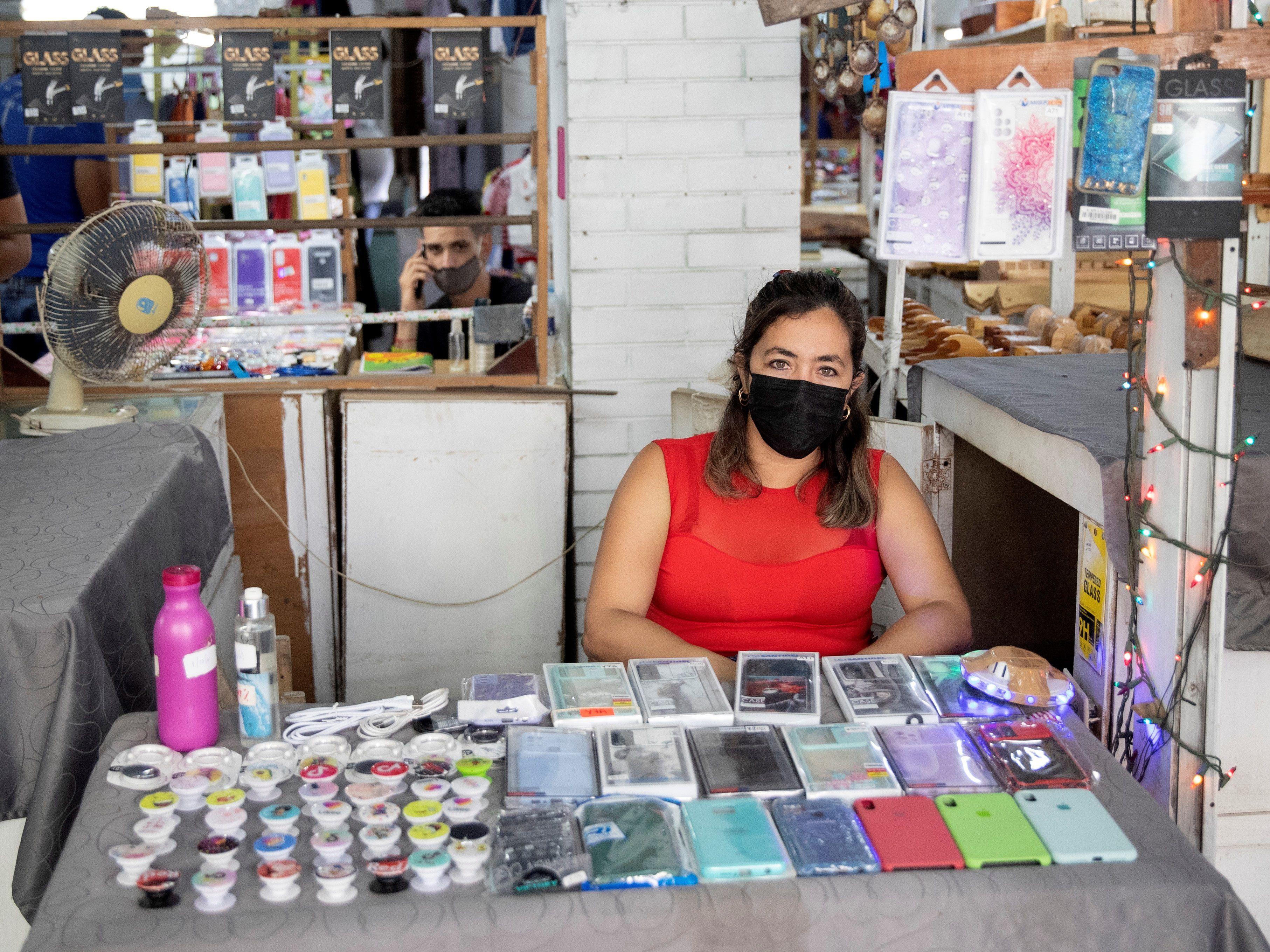 Fotografía de archivo tomada el pasado 8 de octubre en la que se registró a una emprendedora cubana en una feria de trabajadores por cuenta propia, donde exhibe a la venta fundas y otros accesorios importados para celulares, en La Habana (Cuba). EFE/Yander Zamora
