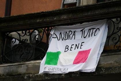 """Una bandera con los colores de Italia y la frase """"Todo estará bien"""" se ve en un balcón de Milán, Italia (Reuters/ Daniele Mascolo)"""