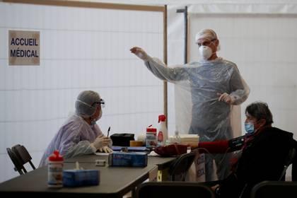 Personal médico, usando trajes protectores y máscaras faciales, habla con un paciente en un centro de emergencia por el COVID-19 dentro de un gimnasio en Champigny-sur-Marne, cerca de París, el 31 de marzo de 2020. REUTERS/Gonzalo Fuentes