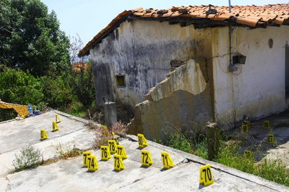Evidence markers are pictured at a crime scene where gunmen killed at least 13 Mexican police officers in an ambush, in Coatepec Harinas, Mexico March 19, 2021. REUTERS/Edgard Garrido