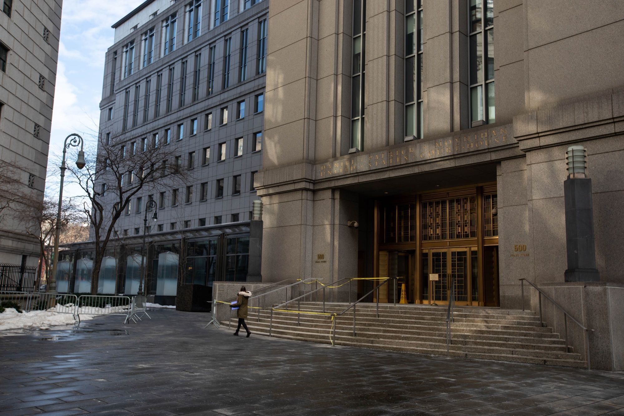 A pedestrian passes in front of the Daniel Patrick Moynihan U.S. District Court for the Southern District of New York Courthouse in New York, U.S., on Monday, Dec. 21, 2020. With vaccinations heralding a return to normalcy, the next year should see courtrooms around the world coming back to life. Ghislaine Maxwell, China critic Jimmy Lai and Samsung heir Jay Y. Lee are among those facing high-profile criminal cases in 2021. Photographer: Michael Nagle/Bloomberg