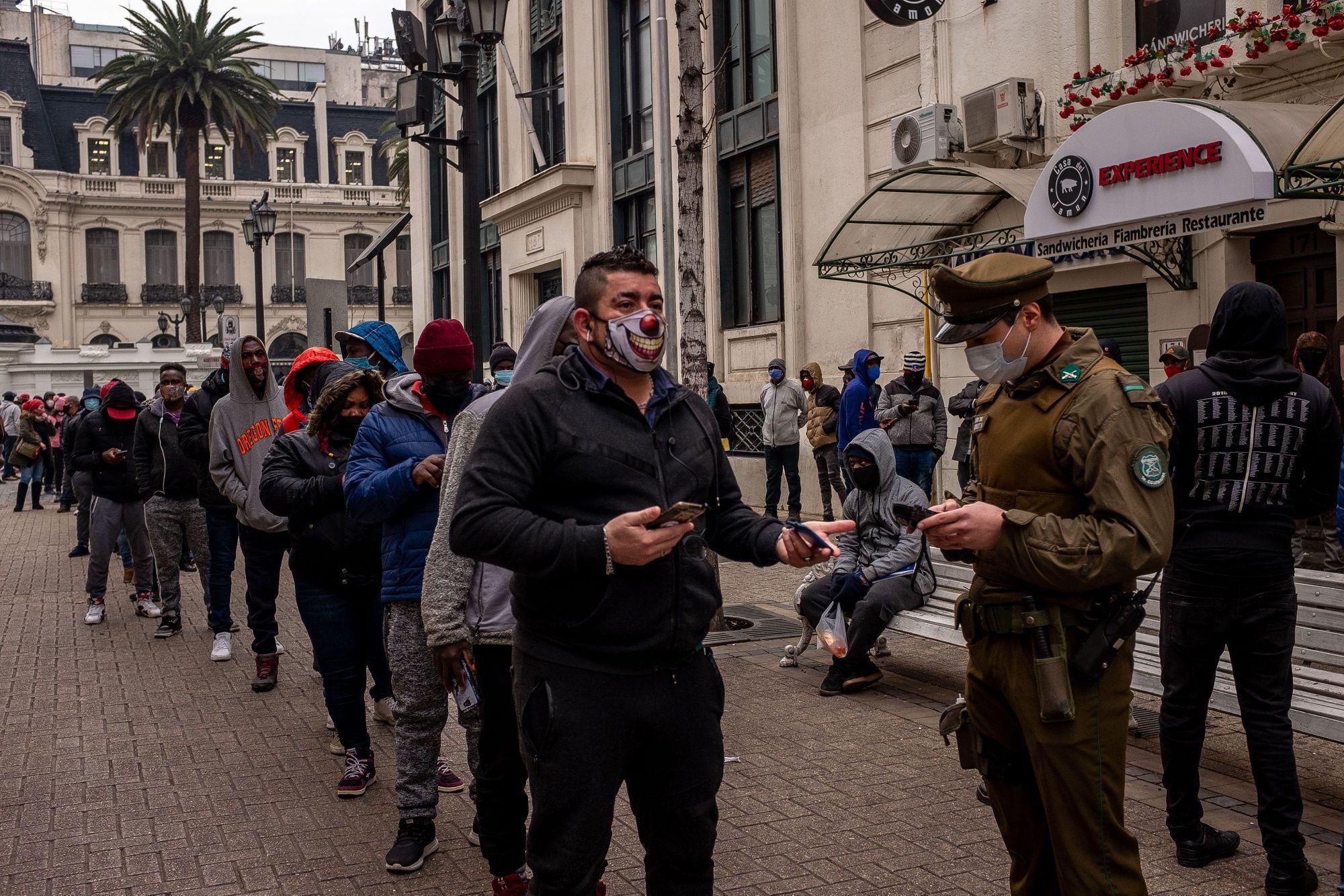 Un carabinero verifica la identificación de una persona en una fila afuera de una oficina de una administradora defondos de pensiones en Santiago, Chile, el lunes 27 de julio de 2020.