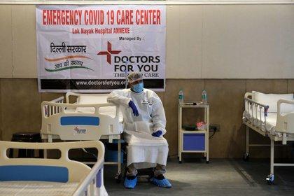 Personal de higiene se sienta al lado de una cama en Lok Nayak Jai Prakash Hospital Annexe en New Delhi . Photographer T. Narayan/Bloomberg