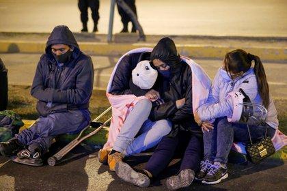 Personas esperan novedades sobre la situación de los heridos durante el operativo en la discoteca, afuera de un hospital en Lima (Reuters)