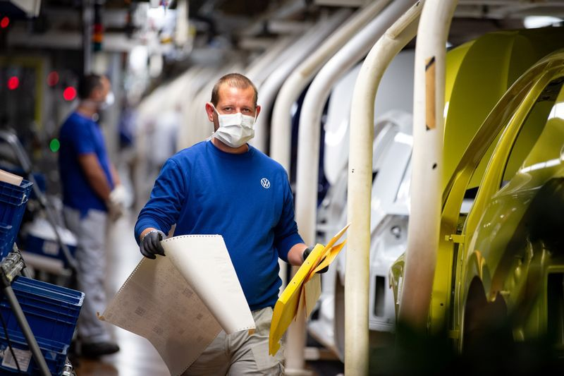 FILE PHOTO: Workers wear protective masks at the Volkswagen assembly line  in Wolfsburg, Germany, April 27, 2020, Swen Pfoertner/Pool via REUTERS