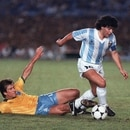 Argentina's Diego Maradona (R) slips past 12 July 1989 Brazilian defender Dunga during first half action of their Copa America final match in Rio de Janeiro. Brazil took an early 2-0 lead. AFP PHOTO/ANTONIO SCORZA (Photo by ANTONIO SCORZA / AFP)