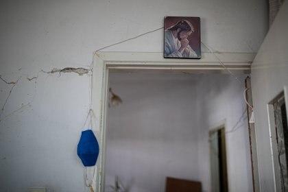 Una mascarilla protectora cuelga de la pared de la casa de Marguerite Dirany que resultó dañada por la explosión en el puerto de Beirut, en el barrio de Karantina, Beirut, Líbano, el 13 de agosto de 2020.