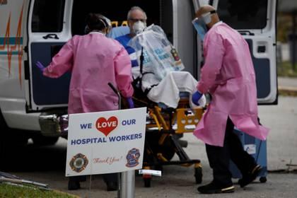 Trabajadores sanitarios atendiendo en Florida a un enfermo con COVID-19  REUTERS/Marco Bello
