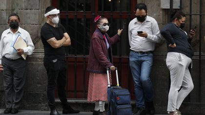 People wearing masks wait in line to enter a bank branch, in central Mexico City, Monday, July 6, 2020. After three months of shutdown, officials allowed a partial reopening of the downtown commercial area last week, although COVID-19 cases continue to climb.(AP Photo/Rebecca Blackwell)