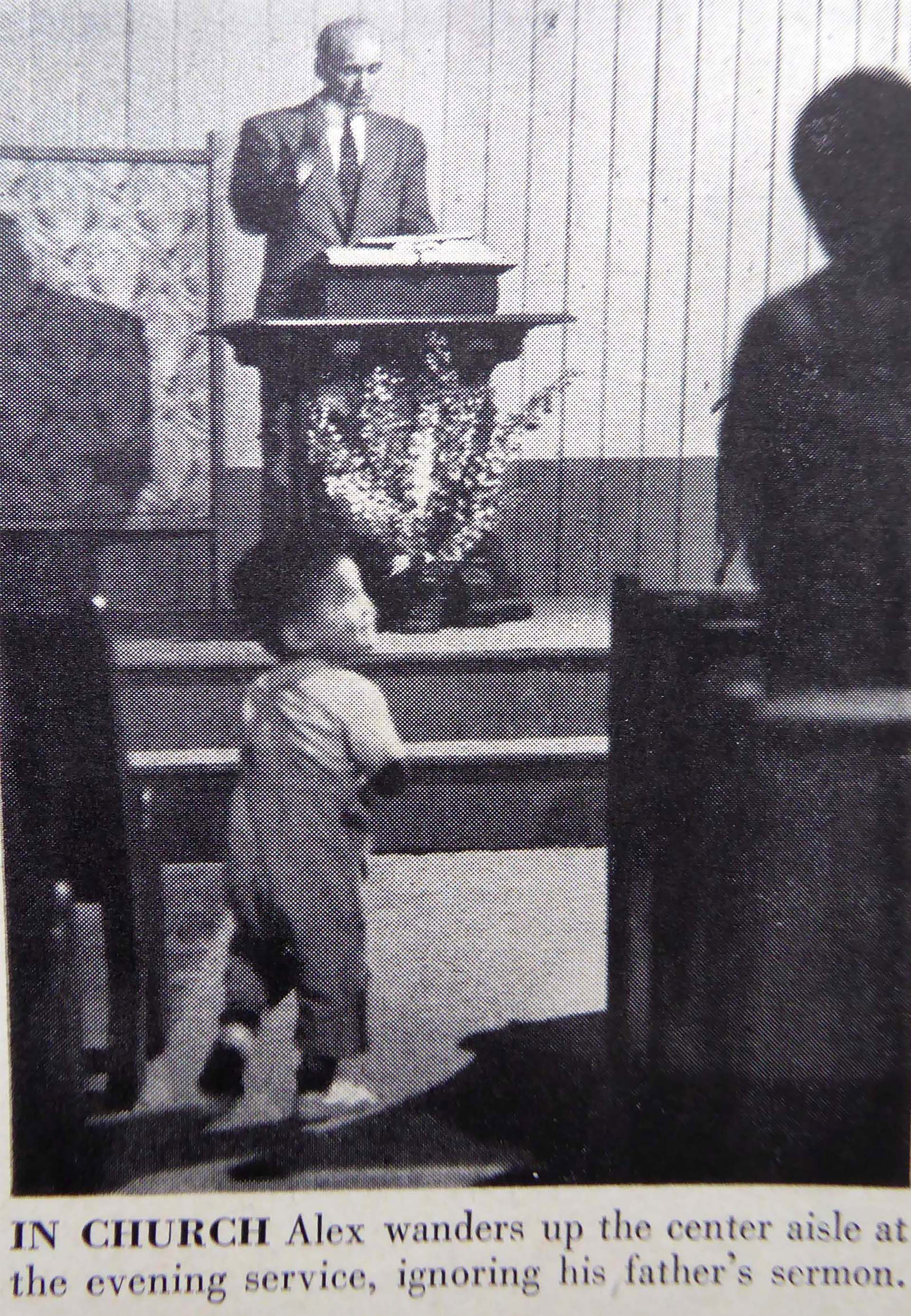 Alexander camina entre los bancos de la Iglesia mientras su padre predica