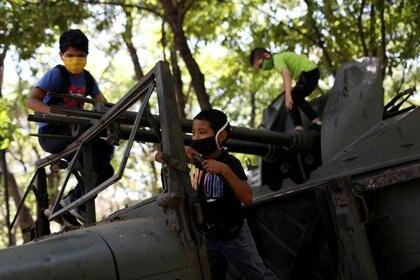 Niños venezolanos juegan en un tanque no operativo en el bulevar Los Proceres en Caracas durante el permiso de 8 horas para que los menores de 14 años salgan al exterior el 26 de abril de 2020 (REUTERS/Manaure Quintero)