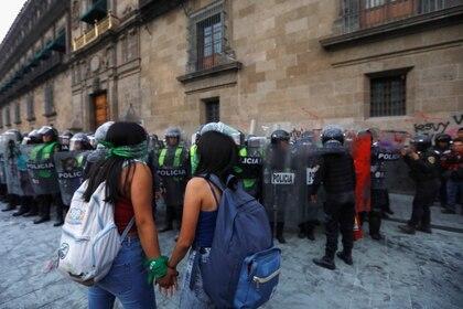 Mujeres se toman de la mano frente a cuerpos de seguridad en Palacio Nacional. (Foto: REUTERS/Mahe Elipe)
