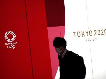 Un hombre que utiliza una mascarilla pasa delante de un tablero decorado con logos de los Juegos Olímpicos de Tokio 2020, en Tokio, Japón  REUTERS/Issei Kato