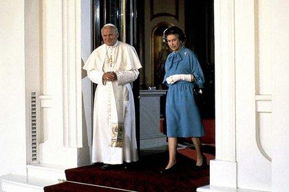 En esta fotografía de archivo del viernes 28 de mayo de 1982, el papa Juan Pablo II camina con la reina Isabel II de Gran Bretaña en el Palacio de Buckingham en Londres