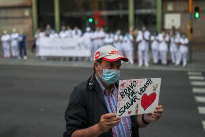 Un hombre agradece al personal sanitario, que organizó una protesta para recuperar el 5% de salario reducido hace una década (Reuters)