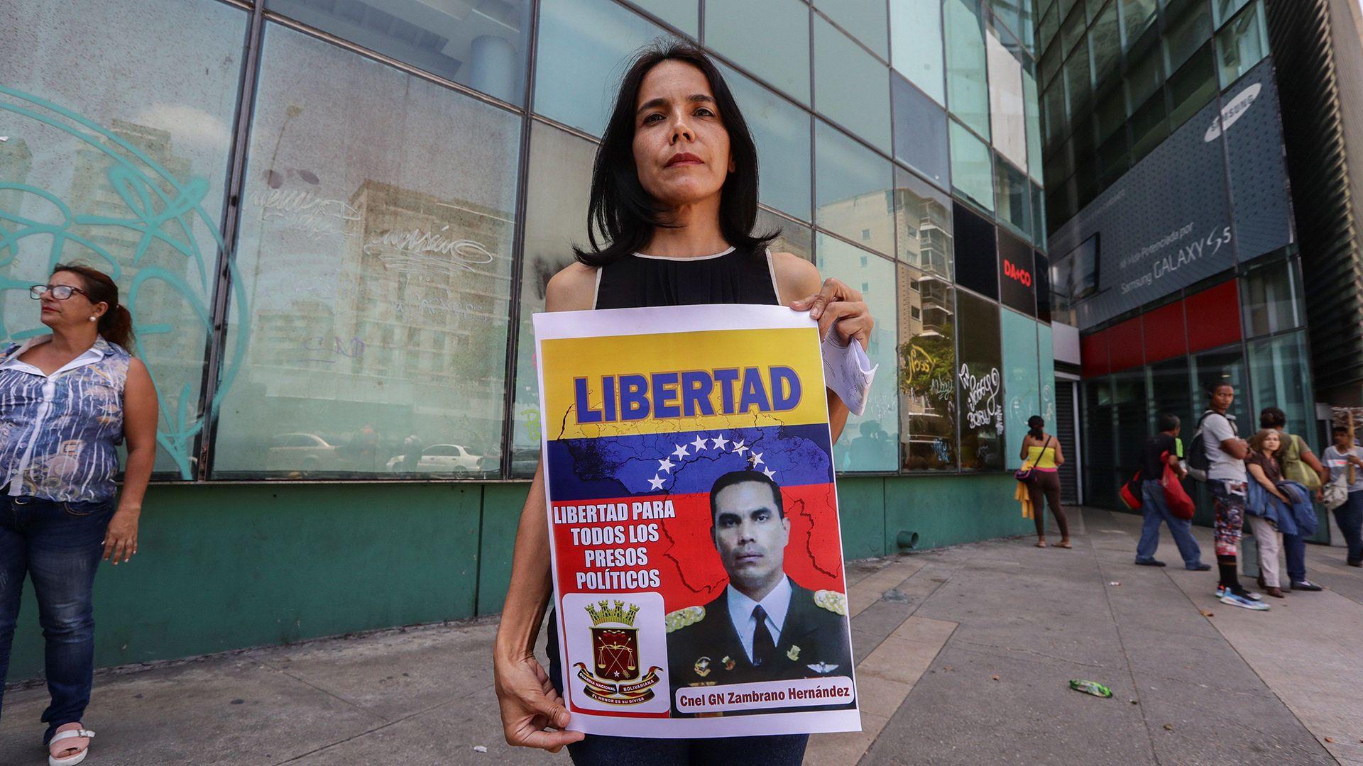 Venecia Zambrano, hermana del coronel preso Pedro Zambrano Hernandez, muestra una pancarta en la sede de la Dirección de Contrainteligencia Militar (EFE/RAYNER PEÑA R.)