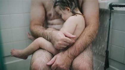 La polémica foto de un padre consolando a su hijo enfermo en la ducha.