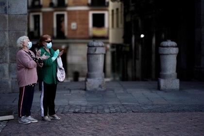 Mujeres mayores con máscaras faciales aplauden en la Plaza Mayor en apoyo a los trabajadores de la salud