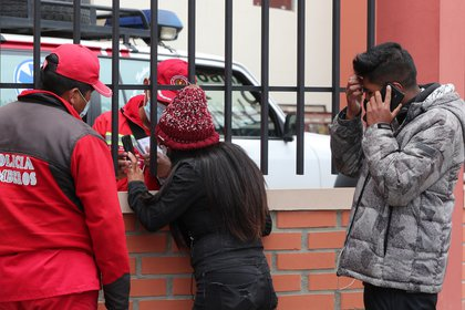 In El Alto (EFE / Martin Alibas) today a firefighter talks to a woman waiting for information after an accident in which several students died.