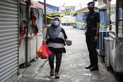 A police officer stands guard at an entrance of a market, during the movement control order due to the outbreak of the coronavirus disease (COVID-19), in Kuala Lumpur, Malaysia March 27, 2020. REUTERS/Lim Huey Teng