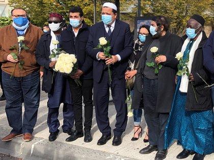 El imán de Drancy Hassen Chalghoumi, presidente de la Conference des imams de France, y una delegación se reúnen con flores cerca del colegio de Bois d'Aulne para rendir homenaje a Samuel Paty (REUTERS/Antony Paone)