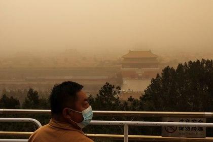 Un visitante con una mascarilla se para detrás de las barricadas en un pico con vistas a la Ciudad Prohibida en el Parque Jingshan, mientras la ciudad es golpeada por una tormenta de arena, en Beijing, China. REUTERS/Tingshu Wang
