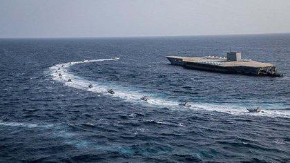 Lanchas de ataque acosan a la maqueta de un portaaviones norteamericano en el Estrecho de Ormuz en lo ejercicios que llevó adelante la Guardia Revolucionaria (AP)