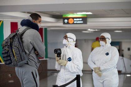 Personal de sanidad controla la temperatura de viajeros ante la pandemia del coronavirus, en el Aeropuerto Internacional de Las Américas, en Santo Domingo (República Dominicana). EFE/Orlando Barría/Archivo
