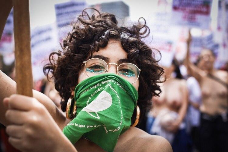 Adelante, los pañuelos verdes, símbolo del reclamo por el aborto legal, seguro y gratuito. De fondo, las mujeres