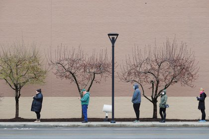 People line up at a safe social distance outside the grocery store amid the coronavirus disease (COVID-19) outbreak in Medford, Massachusetts, U.S., April 4, 2020.   REUTERS/Brian Snyder