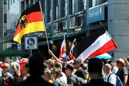 Varios manifestantes ondean la bandera oficial de Alemania y la de los colores imperiales durante las protestas contra las restricciones impuestas por el Gobierno para contener la propagación de la COVID-19 en Berlín, Alemania, el 1 de agosto de 2020. REUTERS/Fabrizio Bensch